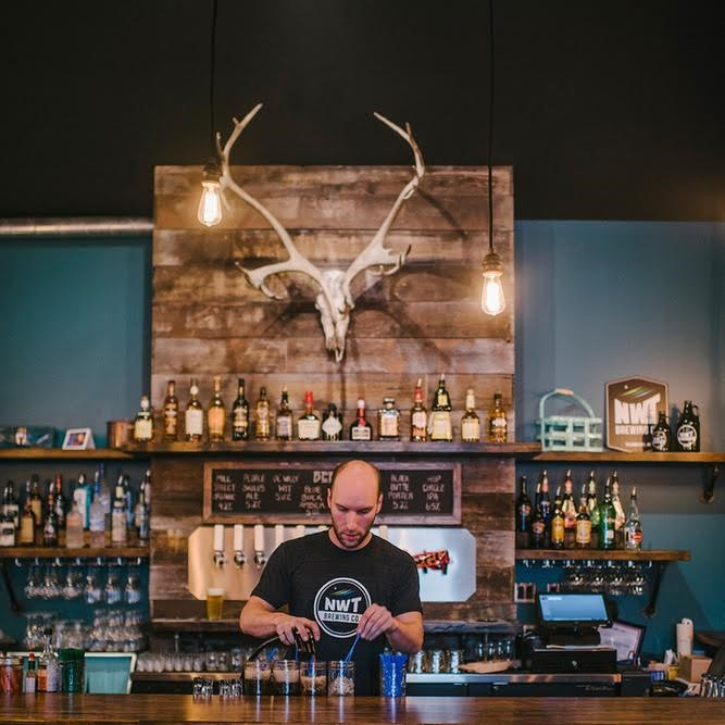 A male bartender stands behind a counter mixing drinks, behind him are an array of bottles and a large skull of a moose mounted to a wooden board