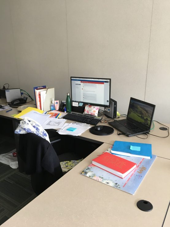 Desk with papers in disarray and laptop open