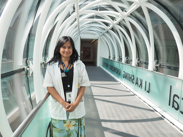 Infectious Disease Specialist Dr. Sharmistha Mishra under the archway at the La Ka Shing Knowledge Institute
