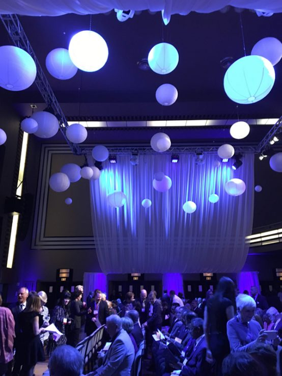 Arbor Award venue at The Carlu with blue back drop and lighting and decorative globes hanging from ceiling