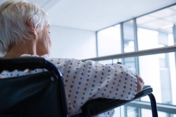 Close-up of senior patient on wheelchair in hospital passageway at hospital