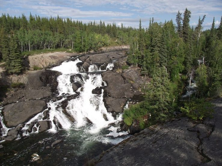 Cameron Falls, cascades down rock formation with coniferous fir trees surrounding it