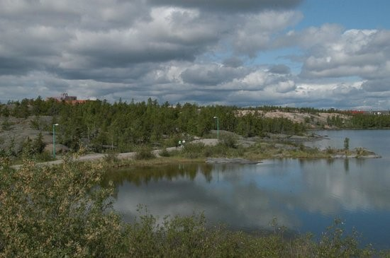 Glassy lake reflecting low clouds on a sunny day, with evergreen trees surrounding it