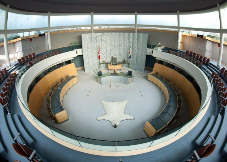 Circular architecture with two levels of chairs, a polar bear rug lies in the centre of the chamber