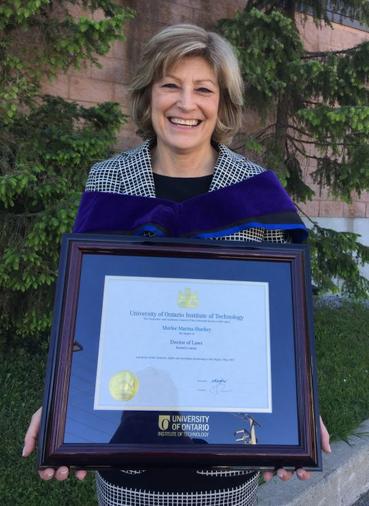 Profile of Shirlee Sharkey standing with her honorary doctor of laws degree framed in front of her