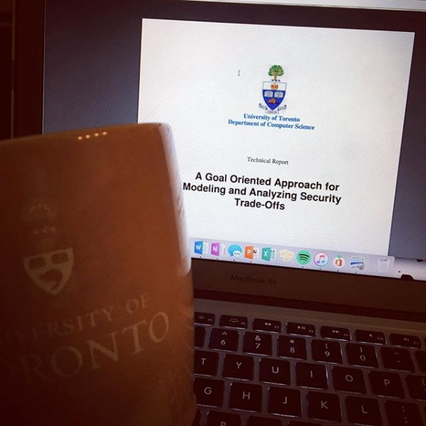 Foreground image of UofT mug, in background image of laptop screen