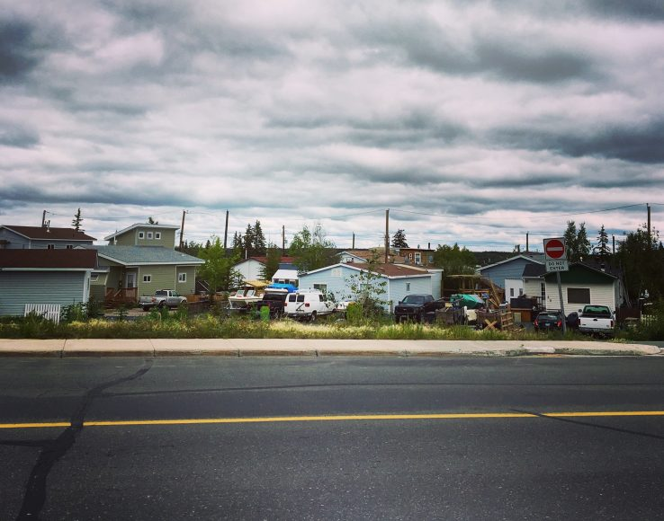 Street in Yellowknife with houses and smoky grey and cloudy sky above