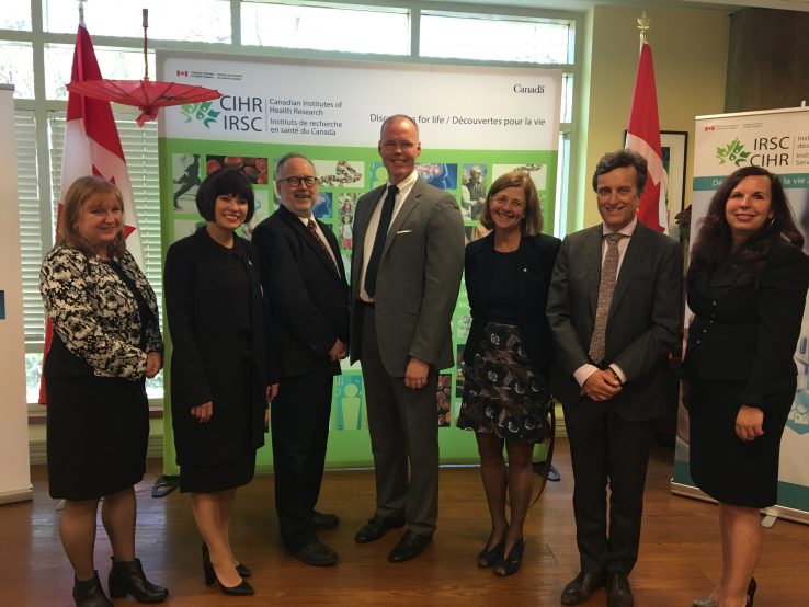 Group of collaborators with Minister of Health Ginette Petitpas Taylor, surrounded by Canadian Flags
