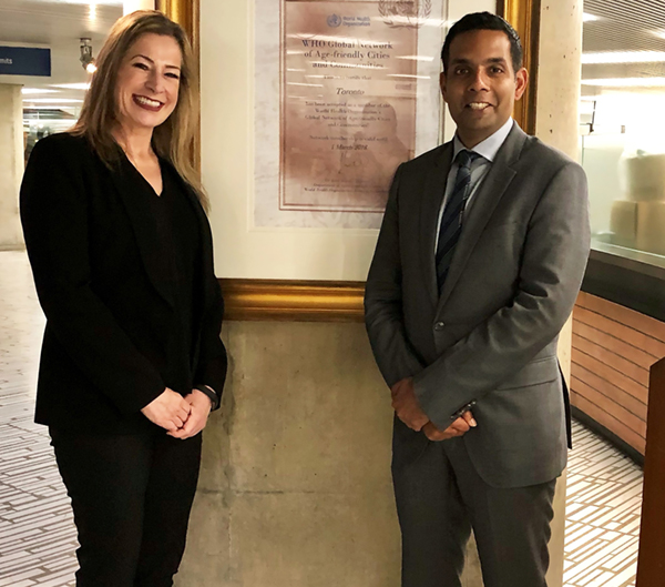 Photo of Andrea Austen Left and Dr. Samir Sinha right in front of pillar at Toronto City Hall