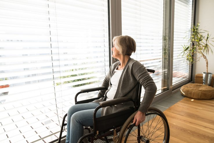 senior woman in wheelchair at home in her living room, looking out the window.