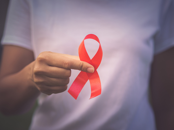 Red color ribbon awareness on young woman hand background: World aids day symbolic concept .