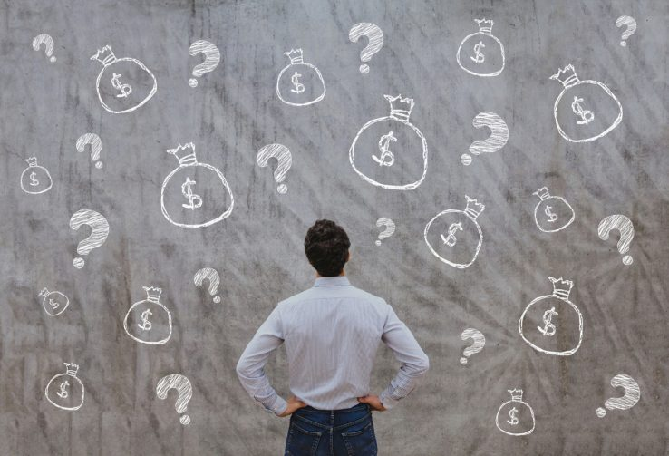 Man looking at chalkboard with illustrations of money bags and question marks