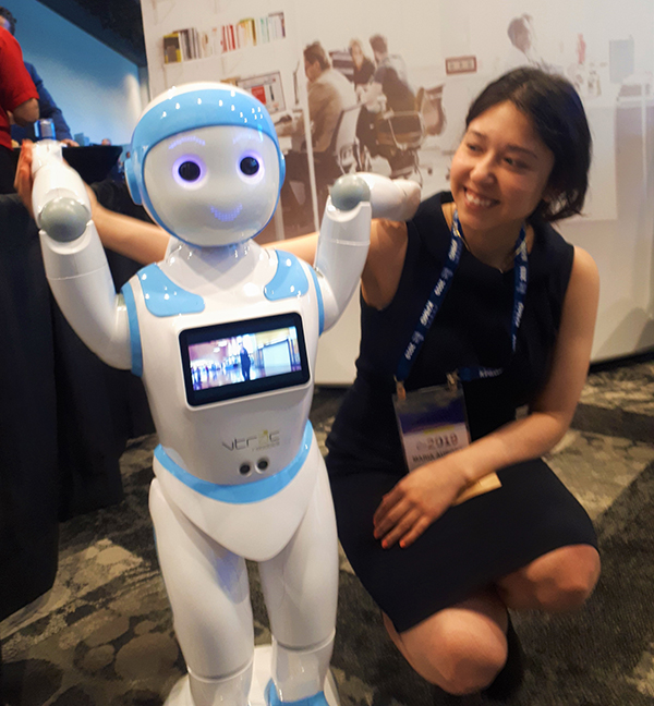 Maria Nunez kneeling at level of humanoid robot that is white and blue
