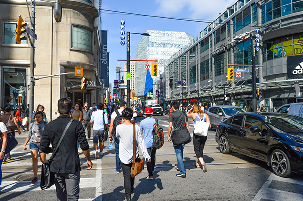 Toronto, Canada - August 30, 2016: Pedestrians crossing a busy intersection near Dundas Square on Queen Street, in Toronto