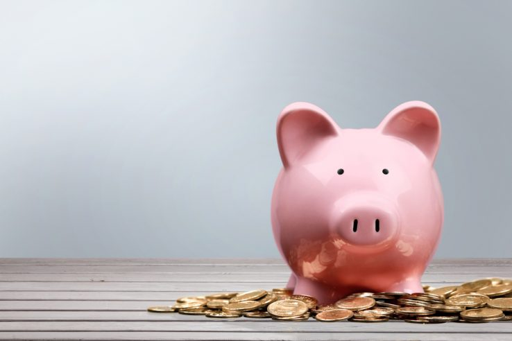 Pink piggy bank and coins on background