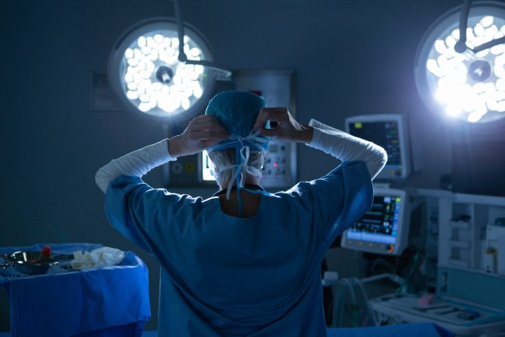 Rear view of female surgeon putting her surgical mask in operating room.